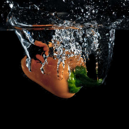 immersed: A yellow chilli pepper splashes into a tank of water.