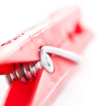 A close-up of a red clothes peg, shot against a white background.