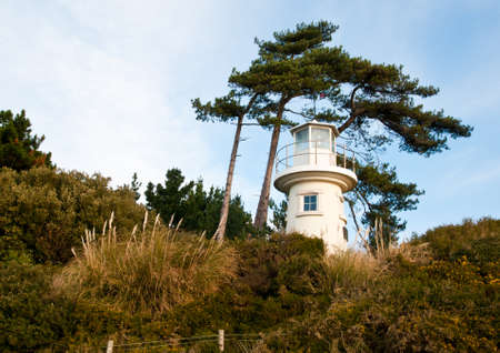 Lepe lighthouse nestled amongst the shrubbery next to the foreshore.