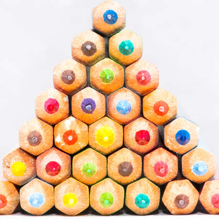 A pyramid of coloured pencils shot against a white background.