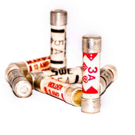 A small collection of three and five amp fuses shot against a white background. Stock Photo