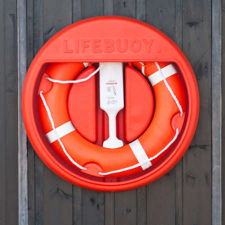 marina life: A red life preserver ring attached to a wall at the marina. Stock Photo