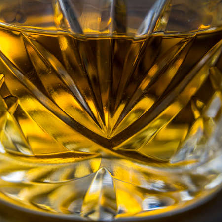 An abstract shot of a cut crystal glass containing Tennessee whiskey
