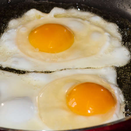 A pair of fried eggs cooking in a frying pan  photo