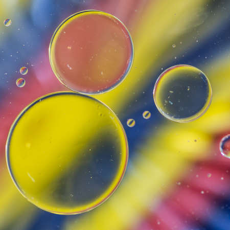 A macro shot of oil floating on water above a colourful background of coloured pencils  photo