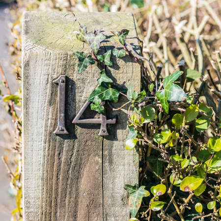 number 14: A shot of a house number fourteen on a garden gate post. Stock Photo