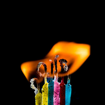 A macro shot of a group of colourful candles burning against a black background