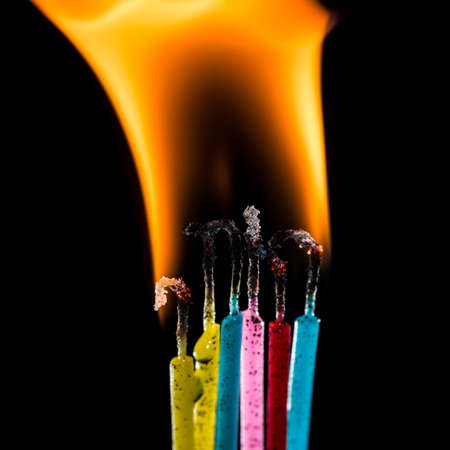 pyromaniac: A macro shot of a group of colourful candles burning against a black background.