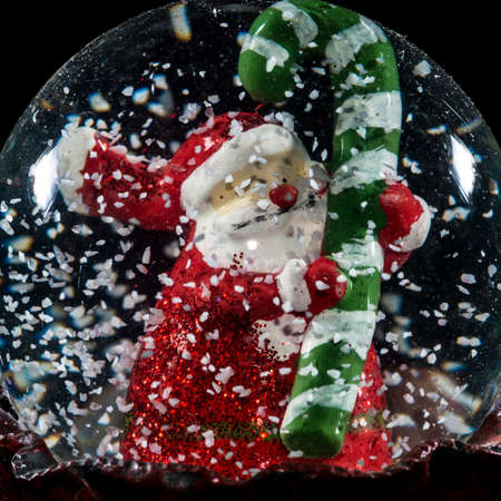 A macro shot of Santa Claus holding a cane within a snow globe. Stock Photo - 24556492