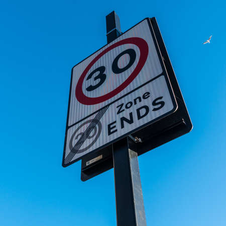 sky is the limit: A speed limit sign set against a blue sky, with a flying gull in the background.