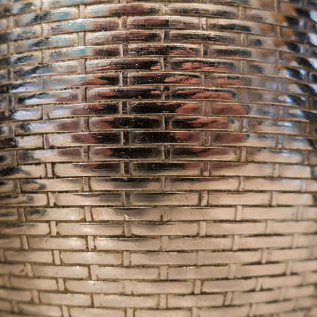 An abstract macro shot of the pattern on the side of a silver teapot.