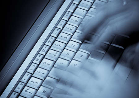 Ghostly hands move across a computer keyboard.
