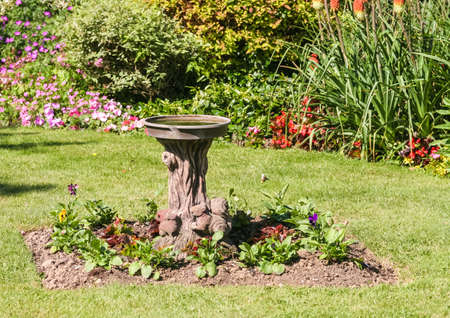 A shot of a bird bath standing in the middle of an English country garden. Stock Photo