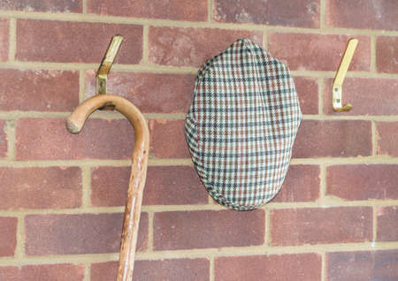 flat cap: A shot of a flat cap and cane hanging on some hooks attached to a brick wall.