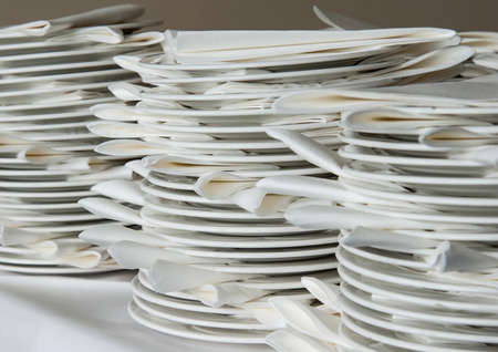 serviettes: A shot of some stacked white plates and serviettes.