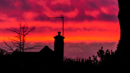 A shot of a silhouetted house against an orange sunset.