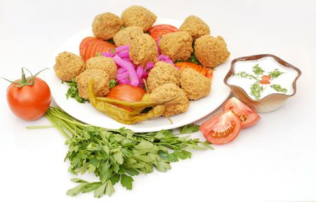falafel in pita bread dressed on a gold lined plate with tomatoes and lettuce with a garnish  photo