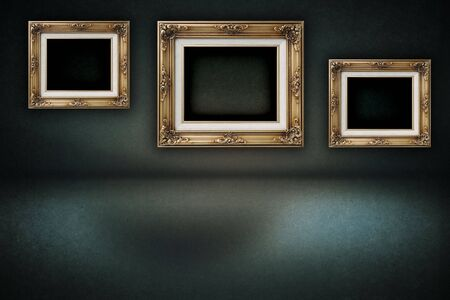 A dark, grungy room with gold frames on the wall  photo