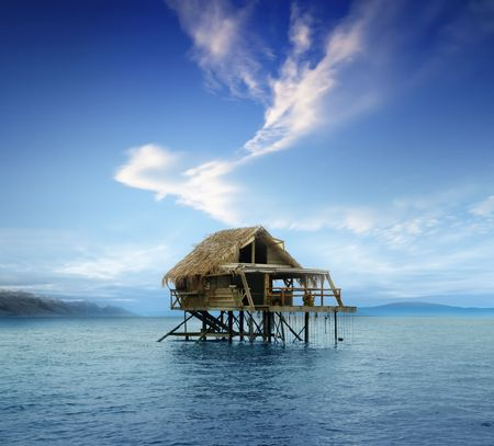 House on wooden stilts in the middle of the ocean photo