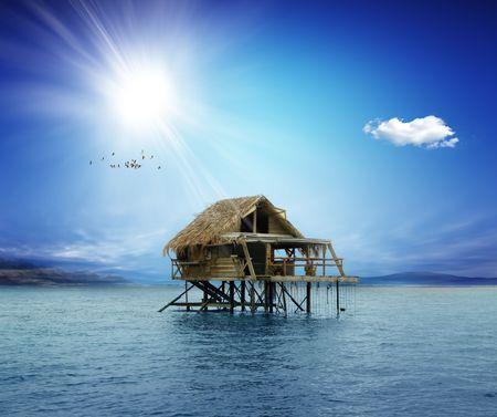 Maison sur pilotis en bois au milieu de l'océan Banque d'images