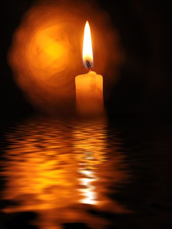 closeup of a burning candle against dark background photo