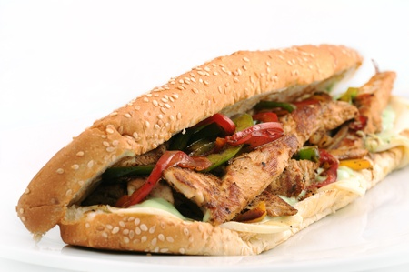 long whole wheat baguette sandwich with meat, vegetables and cheese photo