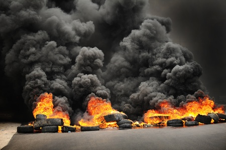 fire car: explosion and burning wheels causing huge dark smoke and pollution Stock Photo