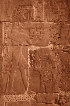 Egyptian hieroglyphs and human figures engraved on stone photo