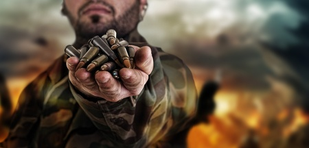 army war concept , military warrior with a handful of bullets against explosion Stock Photo - 12651842