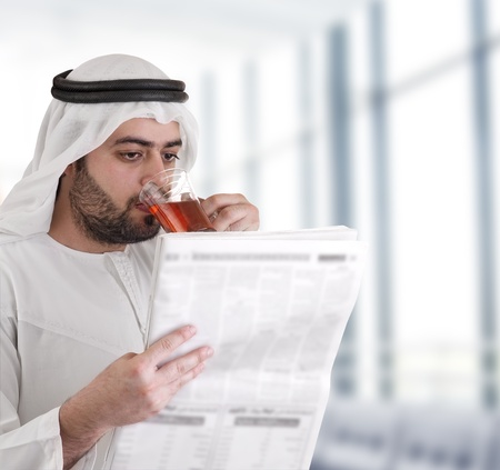 investor: arabian business man drinking tea   reading news-