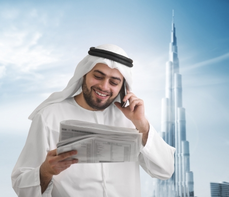 Arabian businessman reading news with burj khalifa photo