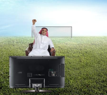 reacting: arabian man watching TV and reacting - front view