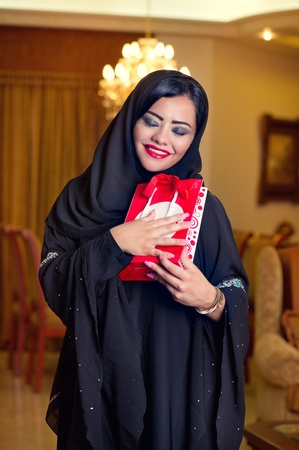 Arabian lady wearing hijab happy for receiving a gift  photo
