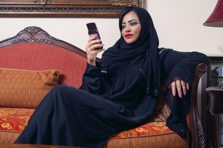 ksa: arabian lady wearing hijab chatting using mobile phone Stock Photo