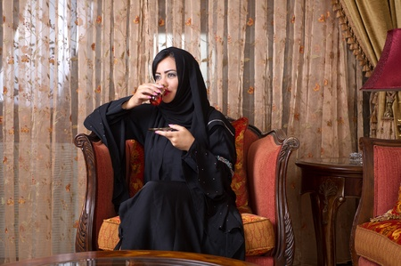 abudhabi: arabian lady drinking tea at home