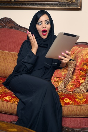 arabian lady with hijab shocked while using a tablet photo