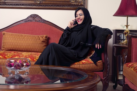 arabian lady wearing hijab talking on mobile at home  photo