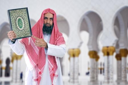 ksa: Arabian Islamic Sheikh presenting holy book of islam Qur an