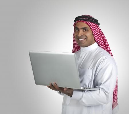 ksa: arabian businessman using laptop in his office
