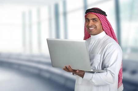 ksa: arabian businessman using laptop in his office