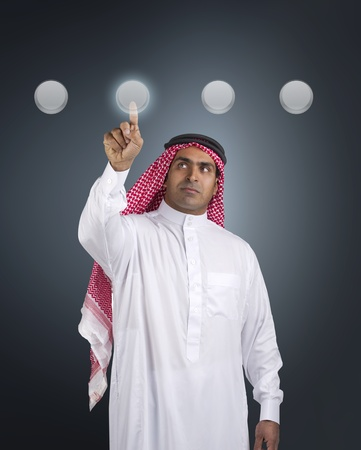 the gulf: arabian businessman pressing a touchscreen button