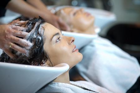 productos de belleza: Hermosa mujer recibiendo un lavado de pelo en una peluquer�a Foto de archivo
