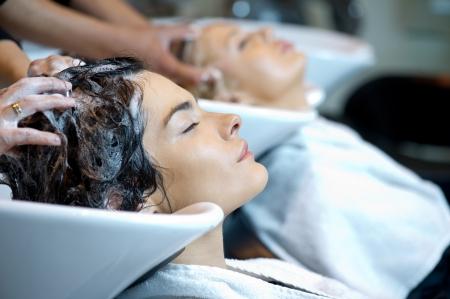 sal�n: Hermosa mujer recibiendo un lavado de pelo en una peluquer�a Foto de archivo