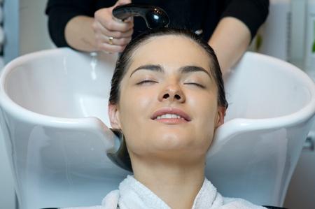 Beautiful woman getting a hair wash  In a hair salon  photo
