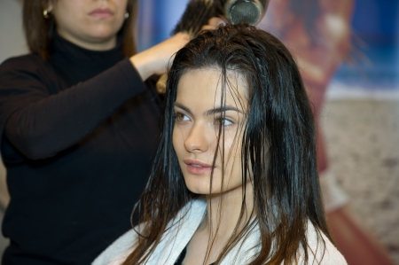 Pretty lady sitting while hairdresser dries her hair  Stock Photo - 13655929