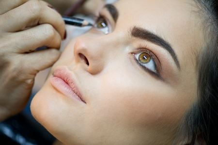 attractive young adult woman applying blusher  photo