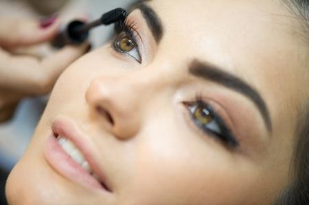 Woman applying mascara on her long eyelashes  Imagens