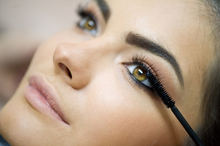 Woman applying mascara on her long eyelashes  Stock Photo