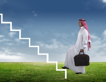 arab man: arabian Businessman stepping up the stairs against a green scene  Stock Photo