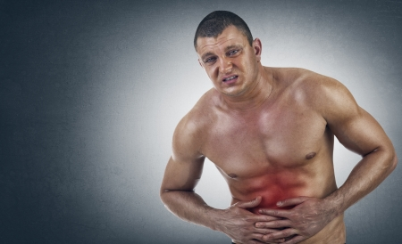 stomach flu: Young Athletic Man in pain